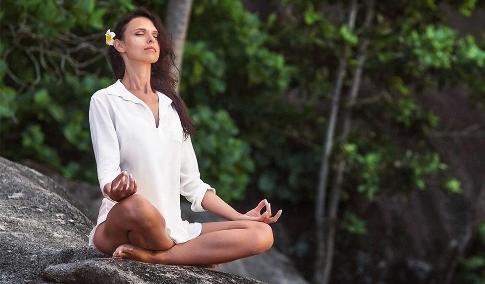 Meditierende Frau auf einem Fels