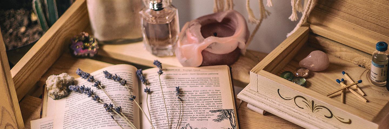 Auf einem Holztisch sind verschiedene Gegenstände angeordnet: Ein Buch, eine Kerze, ein Parfüm-Flakon, mehrere bunte Halbedelsteine, eine Holzschatulle sowie getrockneter Lavendel.