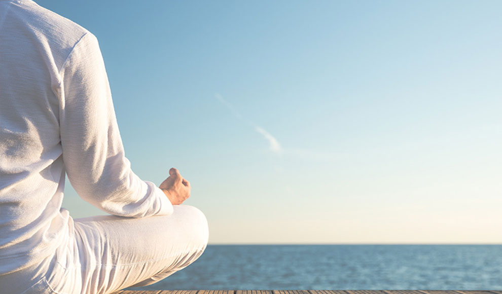 Person in Meditationshaltung am Meer
