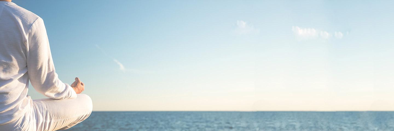 Mann in weißer Kleidung sitzt mit dem Rücken zur Kamera am Meer und meditiert