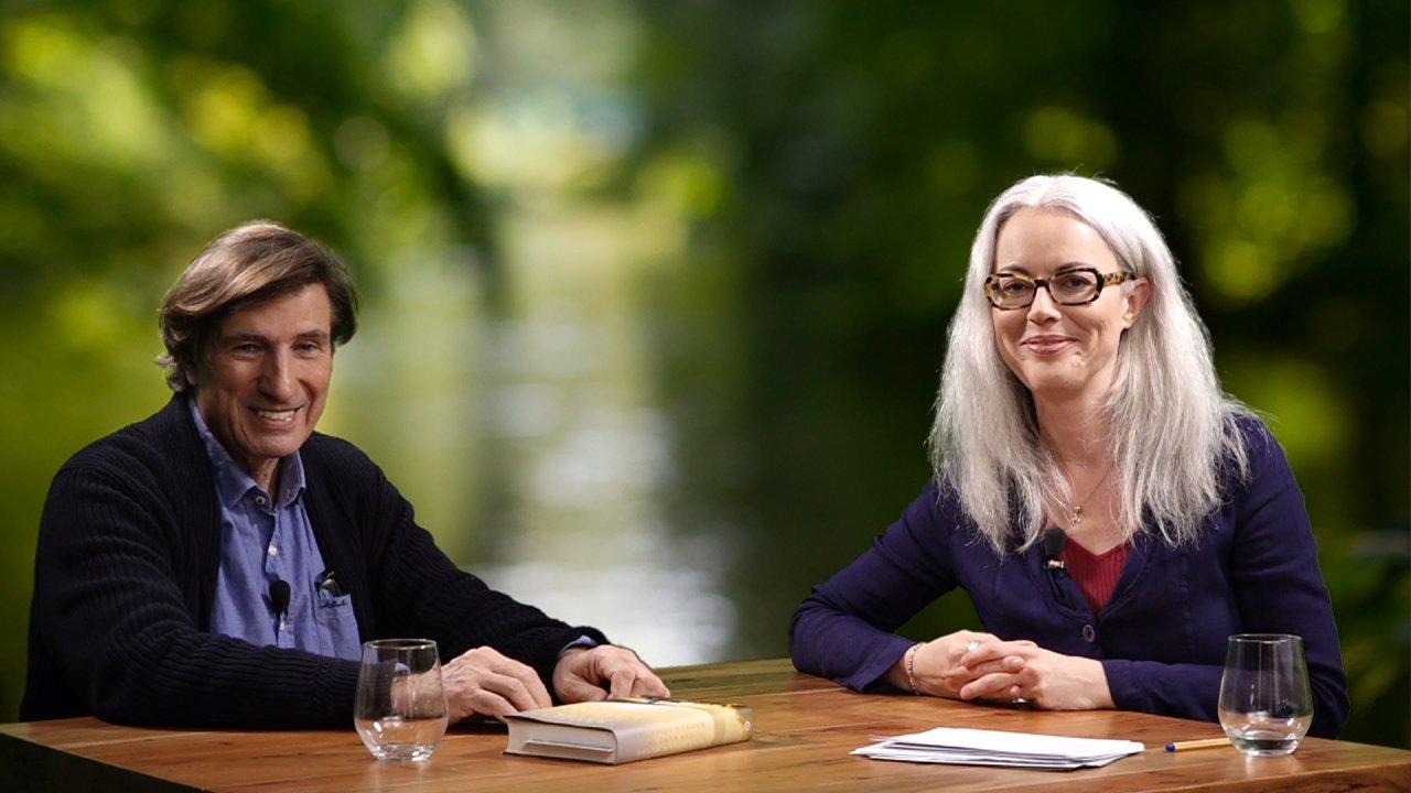 Christian Meyer und die Moderatorin des Webinars sitzen an einem Tisch und blicken in die Kamera