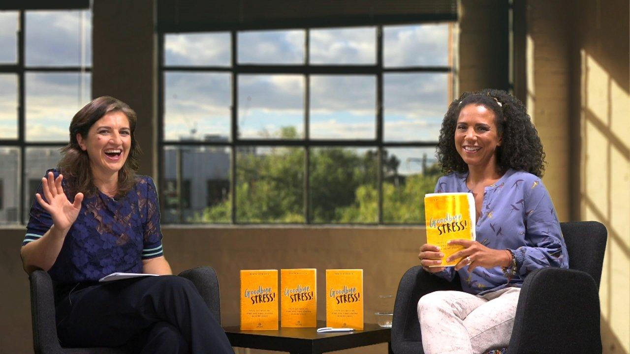 Beata Korioth und die Moderatorin des Webinars sitzen sich in Sessels gegenüber, zwischen ihnen steht das Buch von Beata Korioth auf einem kleinen Tisch. Die Autorin winkt fröhlich in die Kamera