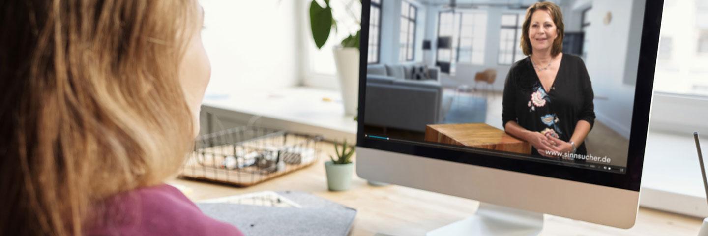 Eine Person sitzt mit dem Rücken zur Kamera vor einem Bildschirm und schaut ein Video zum Online-Kurs mit Stefanie Stahl.