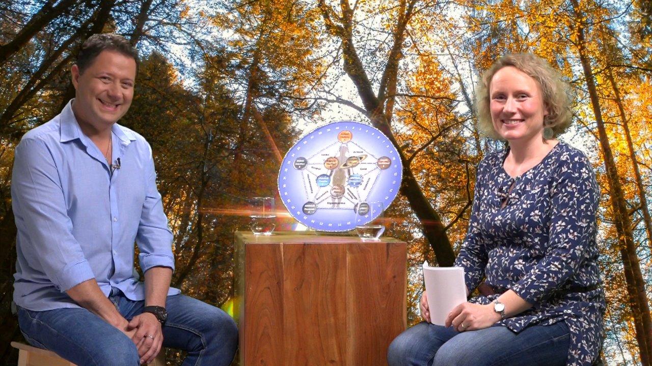 Vadim Tschenze und die Moderatorin des Webinars sitzen sich auf Hockern gegenüber und schauen in die Kamera