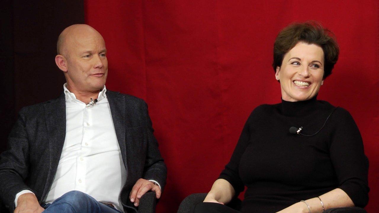 Wolfram und Eva-Maria Zurhorst sitzen nebeneinander vor einer roten Wand. Sie schauen nach rechts.