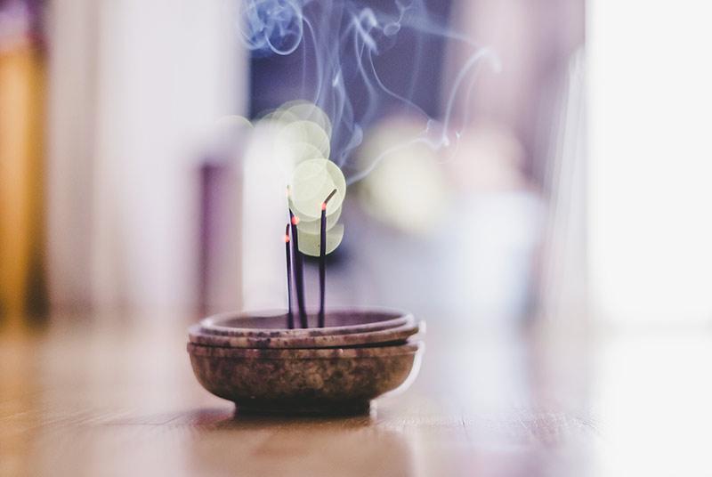 Eine braune Räucherschale steht auf einem Holzboden. Drei Räucherstäbchen brennen darin ab.