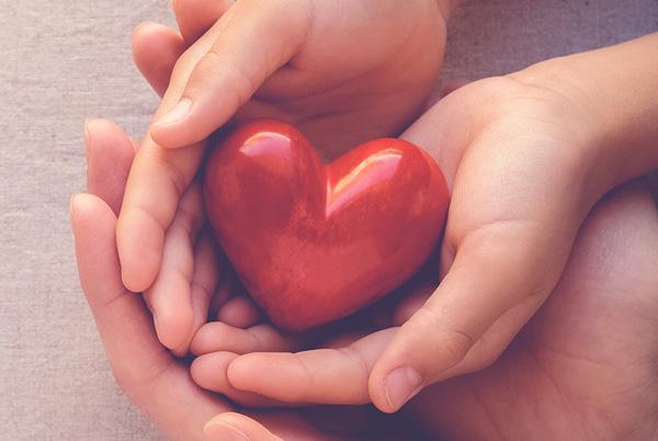 Zwei große und zwei kleine Hände halten zusammen ein rotes Herz