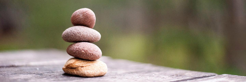 Vier glatte runde Steine wurden auf einem Holzsteg zu einem kleinen Turm aufgeschichtet