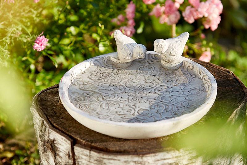 Eine weiße Vogeltränke mit eingeprägtem floralen Muster. Am Rand der Schale sitzen zwei Vögel aus demselben weißen Stein. Die Schale steht auf einem Baumstumpf in einem Garten, im Hintergrund blühen rosa Blumen.