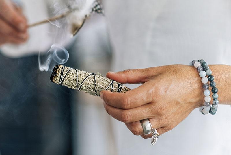 Eine mit Edelstein-Armbändern geschmückte Hand hält ein Büschel weißen Salbei.