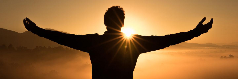 Silhouette eines Menschen mit ausgebreiteten Armen vor untergehender Sonne