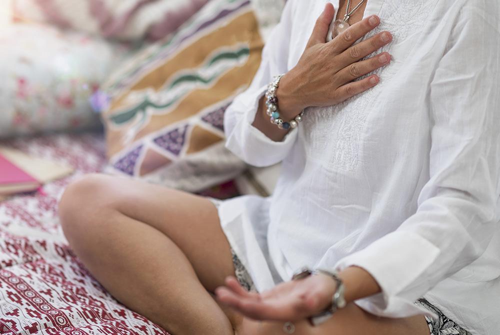 Eine Person in einer weißen Tunika sitzt im Schneidersitz auf einem Bett. Sie hat eine Hand auf ihr Herz gelegt, die andere mit nach oben zeigender Handfläche auf das linke Knie.