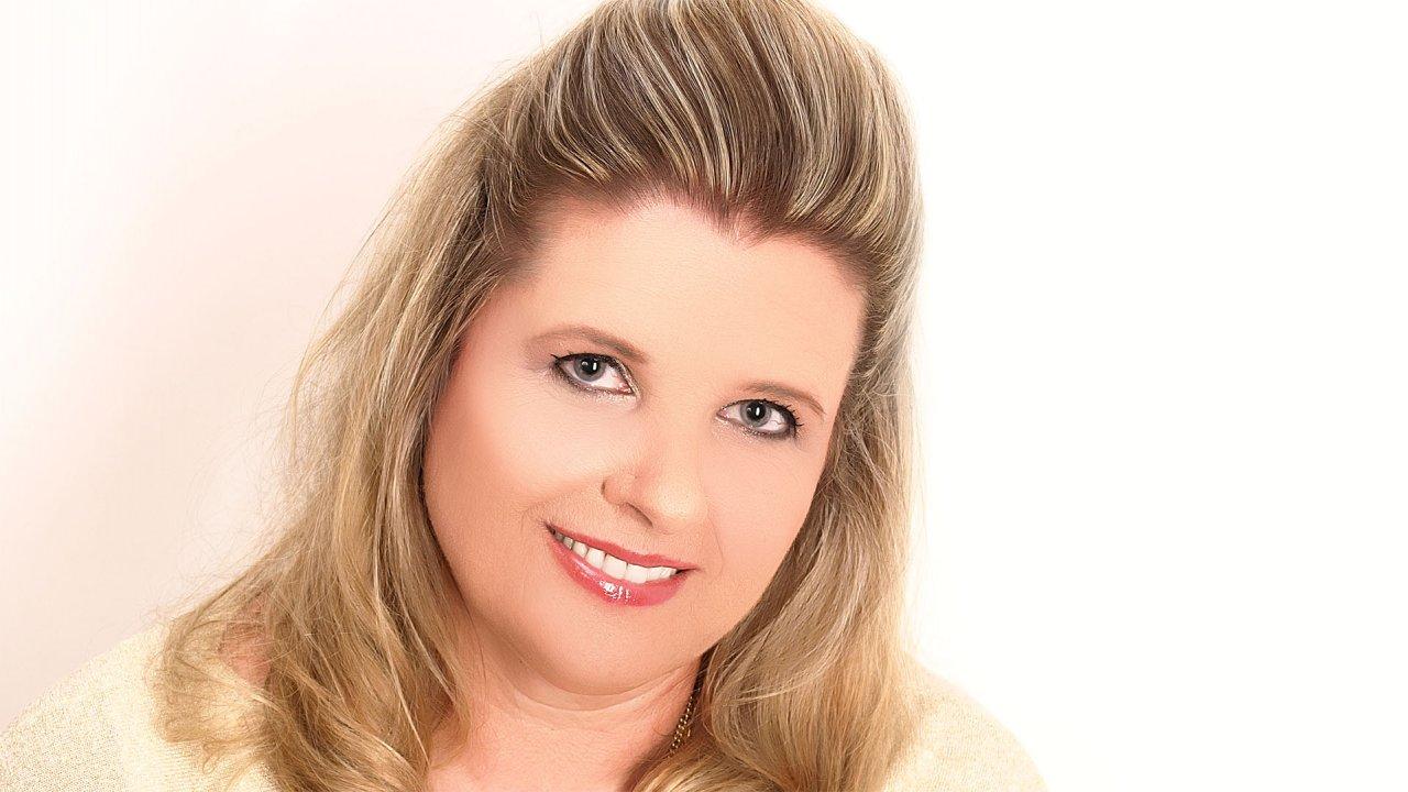 Porträt von Eva-Maria Mora. Sie hält den Kopf schräg und schaut lächelnd in die Kamera